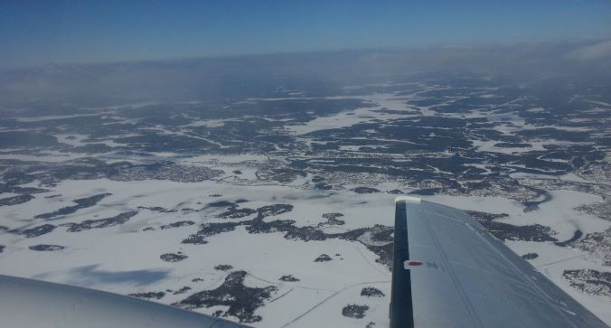 Rat Portage Bay and Safety Bay from the south. Keewatin is left of center, Kenora at the right, behind the wingtip.